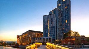 Stort hotellkomplex i flera olika höga nivåer i silhuett mot kvällshimlen. Foto.