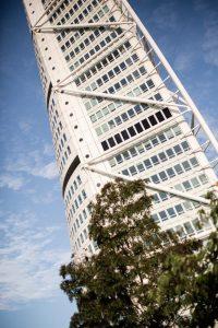 Mycket hög byggnad sedd nedifrån mot blå himmel. Foto.